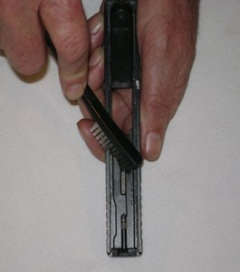 Loosening gunpowder buildup in the slide of a semi-automatic using a nylon brush
